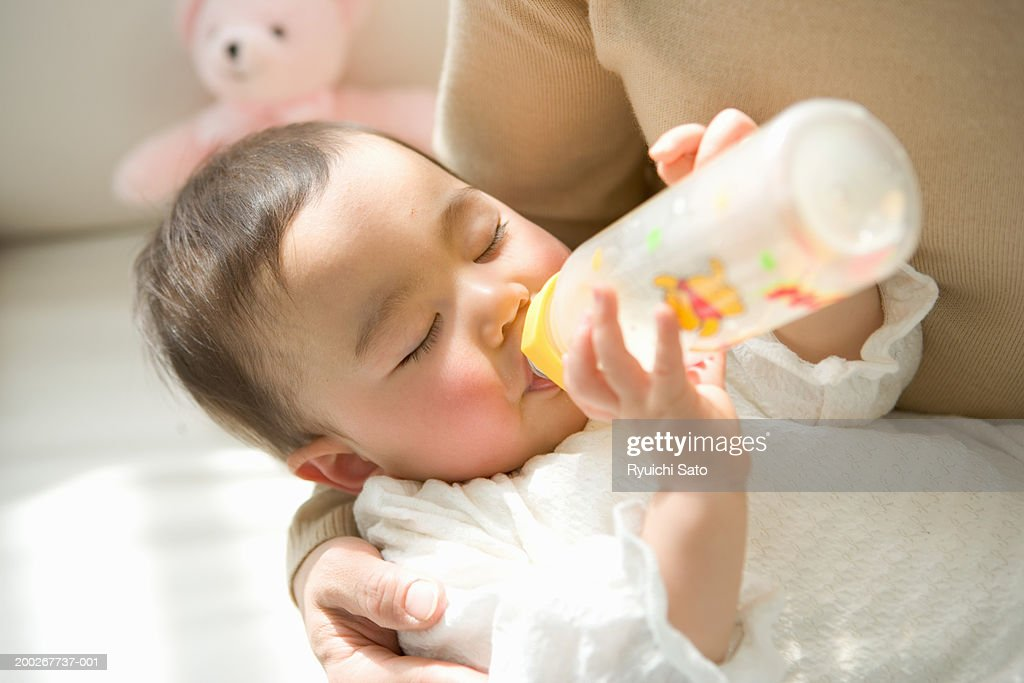 Mother holding daughter (6-9 months) drinking from bottle, eyes closed, close-up : Stock Photo
