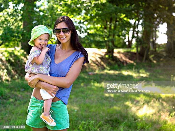 mother holding daughter (18-21 months) in field, smiling, portrait - saint ferme stock photos and pictures