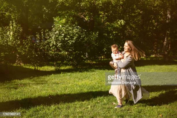 mother holding daughter in hands and running in city park in sunlight. - june stock pictures, royalty-free photos & images