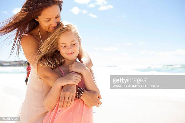 Mother holding daughter in her arms on beach