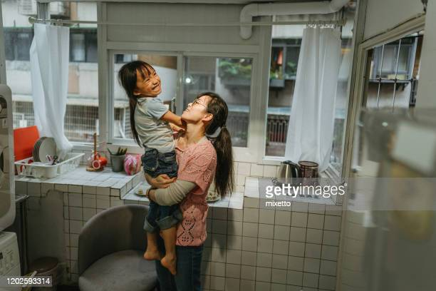 mother holding daughter in kitchen - free mosaic patterns stock pictures, royalty-free photos & images