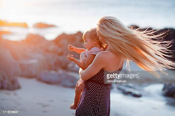 Mother holding daughter on beach