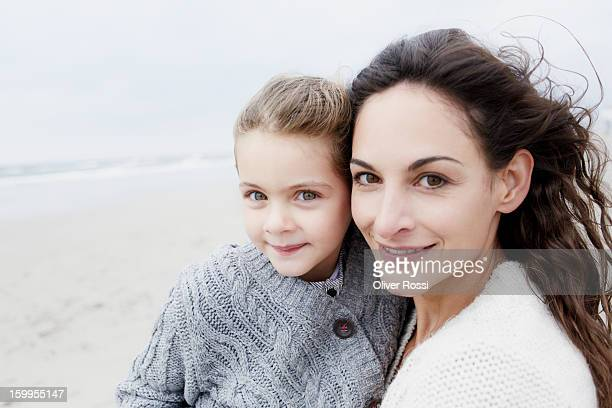Mother holding daughter on the beach, portrait