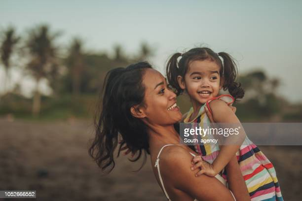 mother holding daughter - indonesia stock pictures, royalty-free photos & images