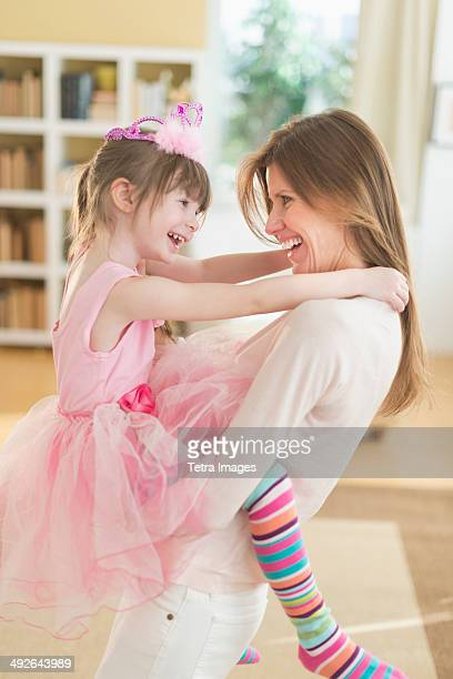 Mother holding daughter (4-5) wearing tutu, Jersey City, New Jersey, USA