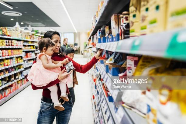 mother holding daughter while shopping - vietnamese ethnicity stock pictures, royalty-free photos & images