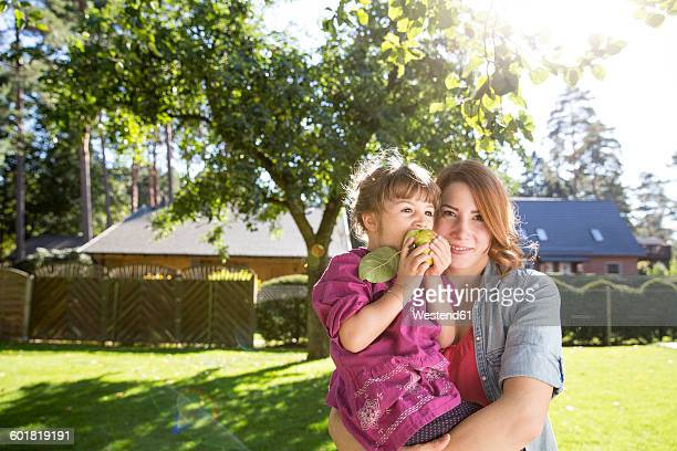 Mother holding daughter with apple in garden