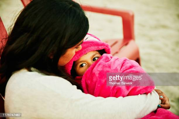 mother holding daughter wrapped in blanket during family beach party - hot pink stock pictures, royalty-free photos & images