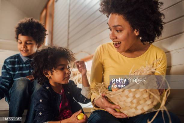 mother holding easter eggs for her children - easter photos stock pictures, royalty-free photos & images
