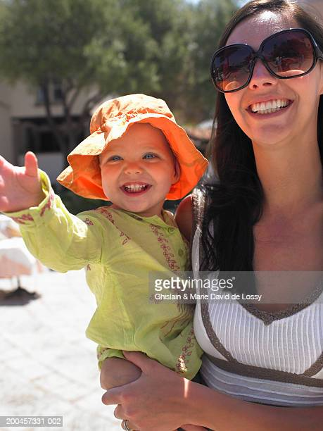 Mother holding female toddler (15-18 months), girl waving