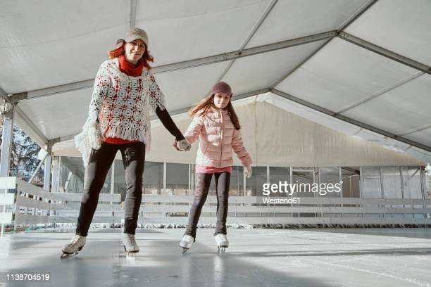 mother holding hand of her daughter , while ice skating - ice rink stock pictures, royalty-free photos & images