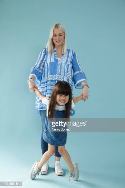 mother holding hands with daughter against pale blue background - nerys jones stock photos and pictures