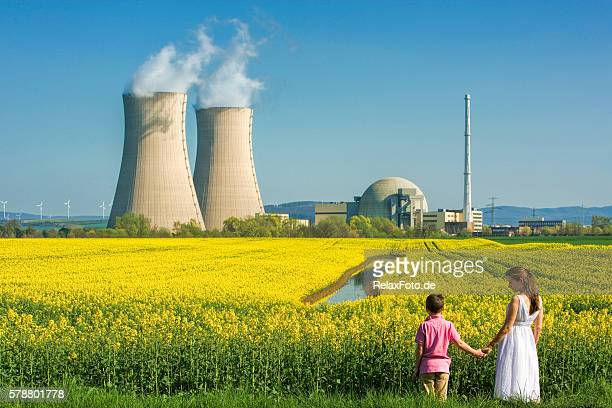 mother holding hands with son at nuclear power station - nuclear power station stock pictures, royalty-free photos & images