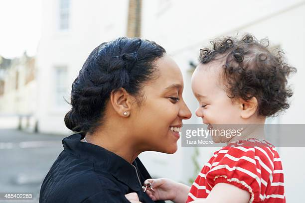 mother holding happy child - leanincollection stock pictures, royalty-free photos & images