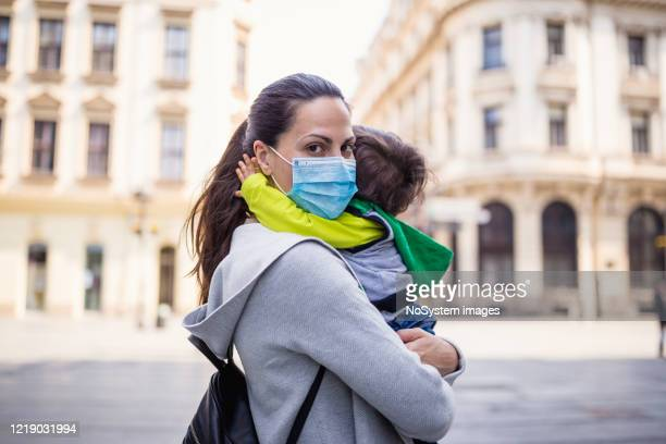 mother holding her baby boy wearing protective mask - empty streets stock pictures, royalty-free photos & images
