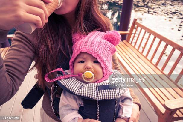 Mother holding her baby girl in baby carrier while drinking coffee