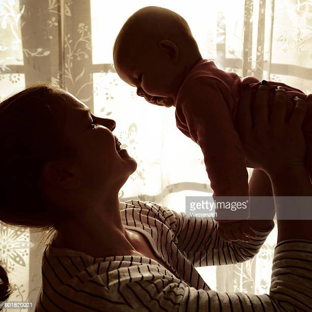 Mother holding her baby up in the air in front of a window