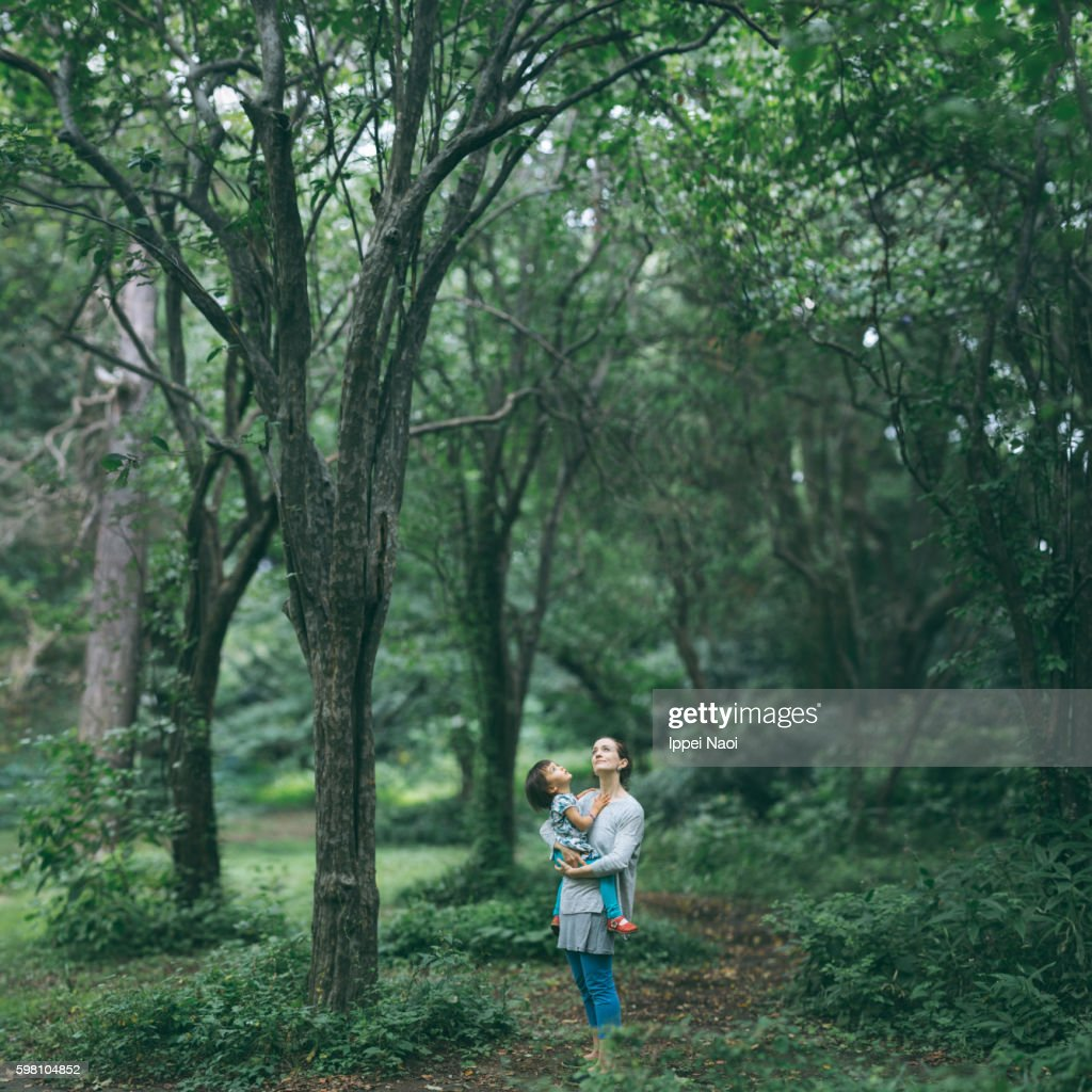 Mother holding her child and looking up at tree canopy : Stock Photo
