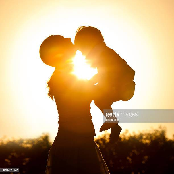 Mother holding her child at sunset