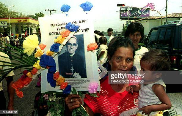 A mother holding her child walks through the streets of the Salvadoran capital 24 March 1993 with a portrait of slain San Salvador Archbishop Arnulfo...