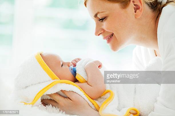 Mother holding her clean baby boy wrapped in towel
