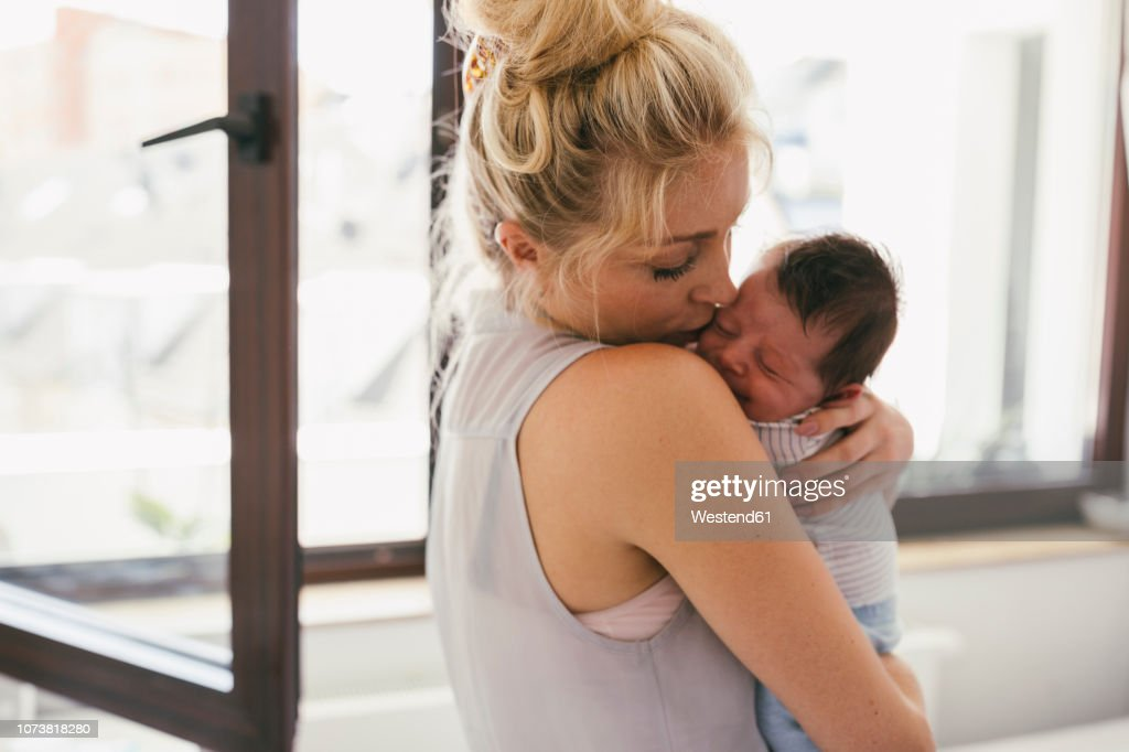 Mother holding her crying baby close to her shoulder at home : Stock Photo