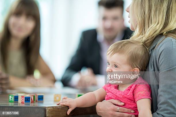 Mother Holding Her Daughter During a Meeting