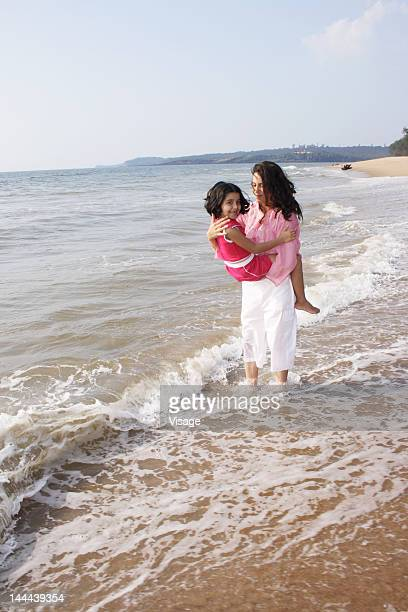 Mother holding her daughter on the Beach