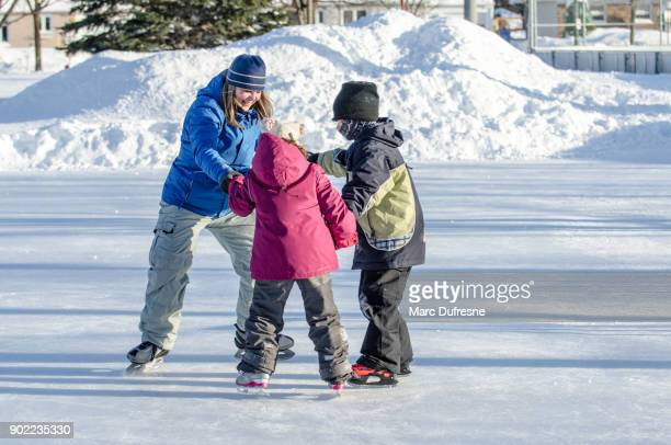 Mother holding her daughter's and son's hands to help them ice skating in circle