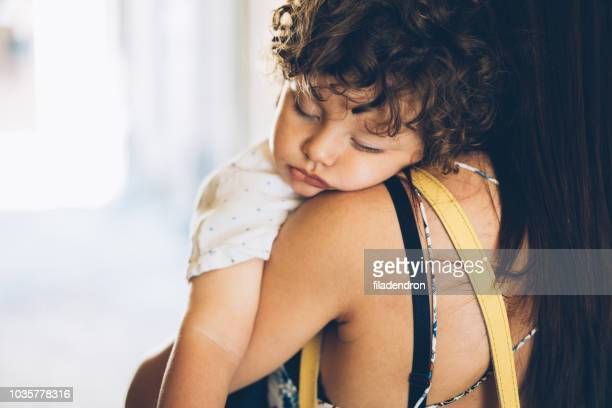 mother holding her sleeping son - nanny stock photos and pictures