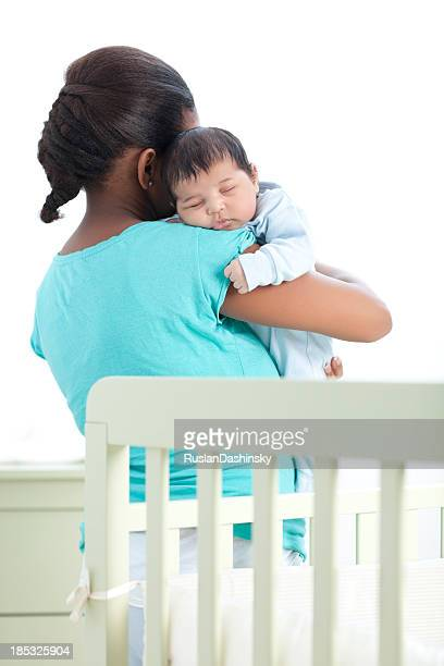 Mother holding her sleeping son.