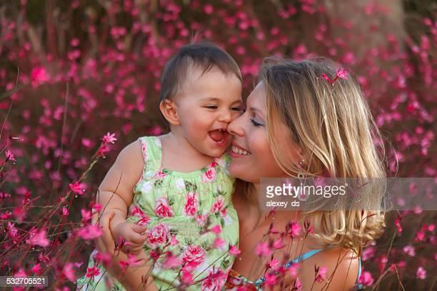 Mutter hält ihr lächelnd baby Mädchen in den Armen