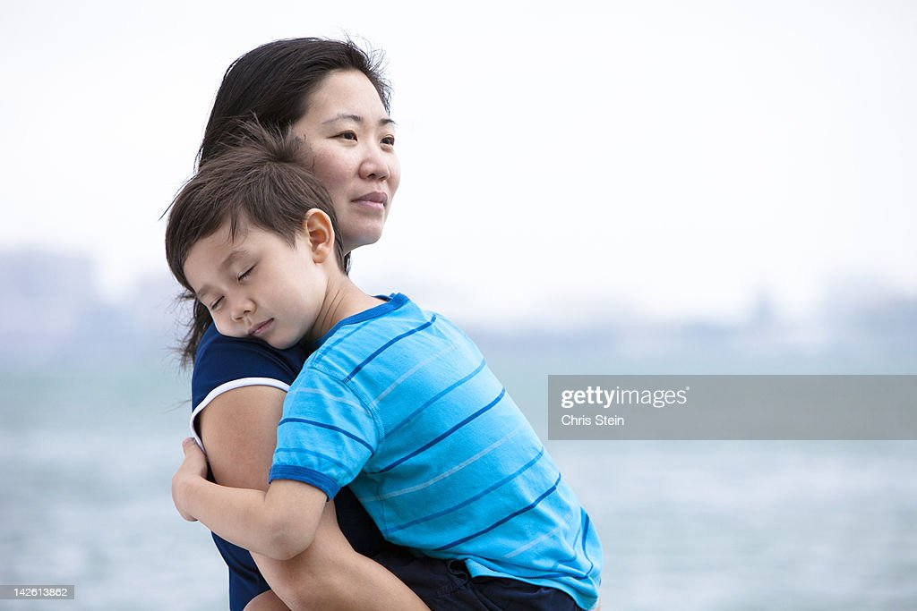 Mother holding her son at the beach : Stock Photo
