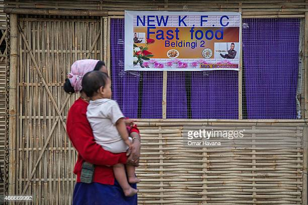 A mother holding her son passes by a fast food shop opened by refugees inside the Beldangi 2 refugee camp on March 14 2015 in Beldangi Nepal More...