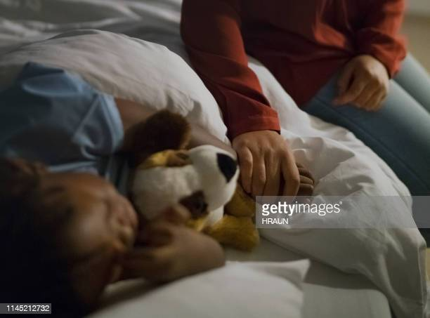 mother holding ill son's hand sleeping on bed - stuffed toy stock pictures, royalty-free photos & images