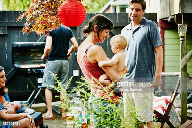 Mother holding infant daughter during barbecue