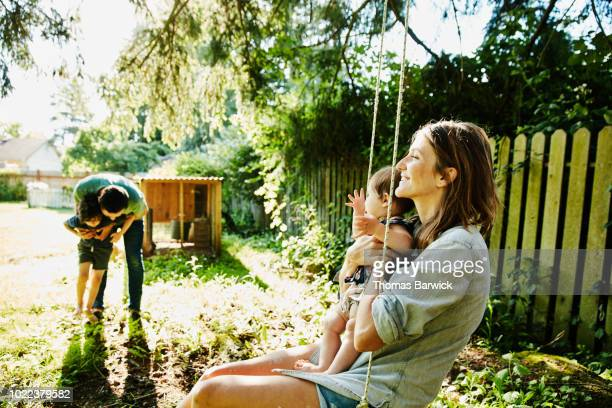 mother holding infant daughter on swing while father plays with son in backyard - ungestellt stock-fotos und bilder