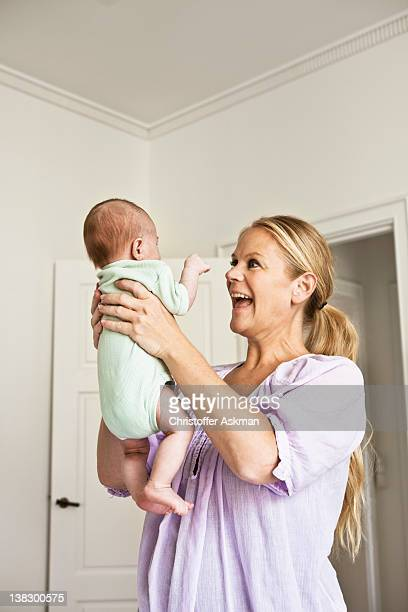Mother holding infant in bedroom