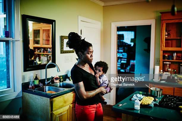 Mother holding infant in kitchen after dinner