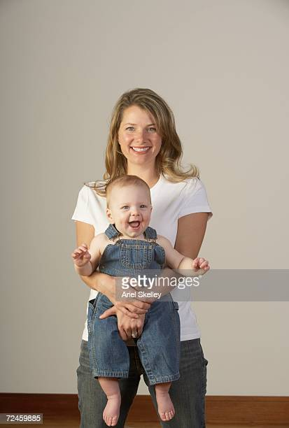 Mother holding laughing baby in overalls