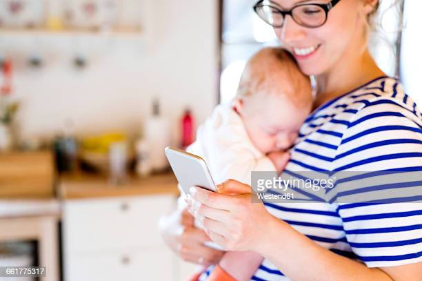Mother holding little baby looking at cell phone