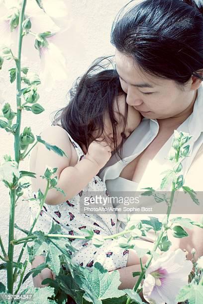 Mother holding little girl, little girl resting head on mother's shoulder