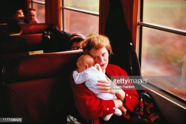 mother holding new son on a train - image stock-fotos und bilder