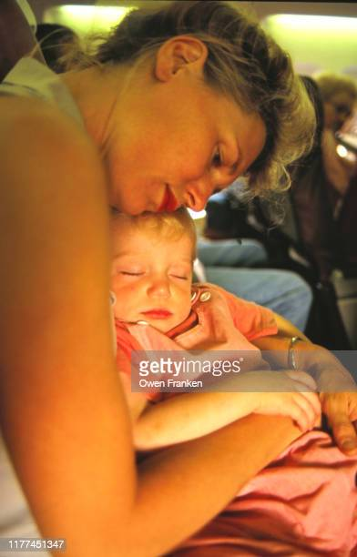 mother holding new son on a train - image stock pictures, royalty-free photos & images