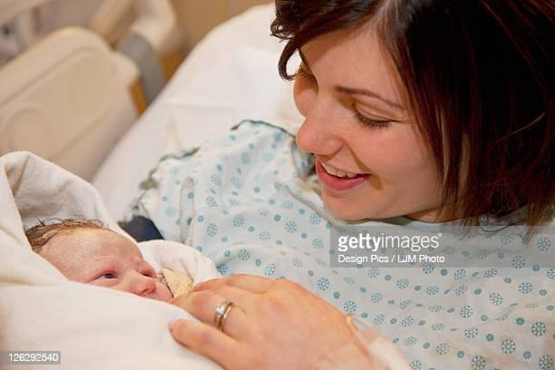 mother holding newborn baby daughter