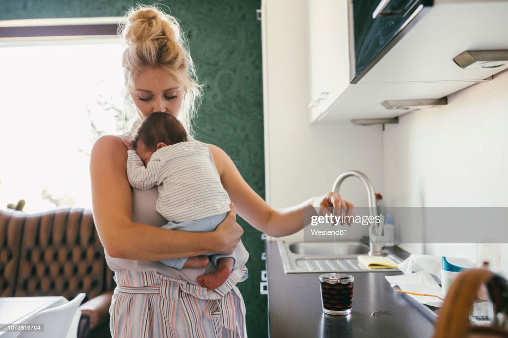 Mother holding newborn baby in kitchen while making tea : Stock Photo