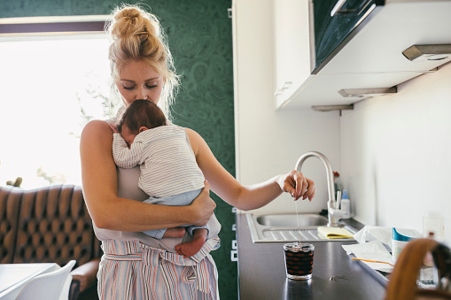Mother holding newborn baby in kitchen while making tea - gettyimageskorea