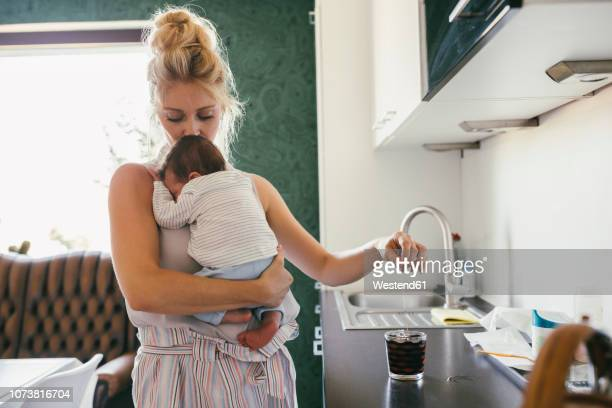 mother holding newborn baby in kitchen while making tea - baby stock-fotos und bilder