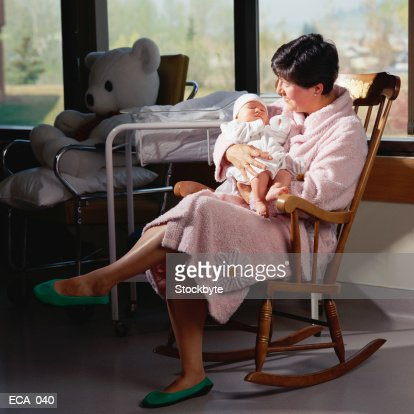 Mother Holding Newborn Baby Sitting In Rocking Chair High