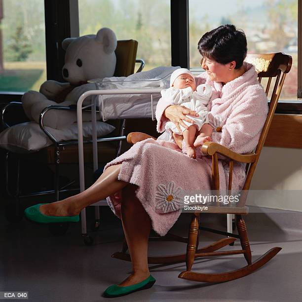 Mother holding newborn baby, sitting in rocking chair